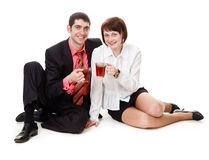 Young, smiling, woman and man, drinking tea. Young, smiling, woman and man sitting on the floor, drinking tea, isolated on a white background Royalty Free Stock Photos