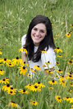 Young smiling woman in meadow with yellow flowers Royalty Free Stock Photos