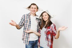 Young smiling woman, man in casual clothes and newspaper hats spreading hands. Happy couple isolated on white background stock photos
