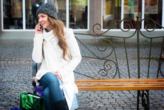 Young smiling woman with mobile phone. Young smiling woman sitting on berm calling with mobile phone Royalty Free Stock Images