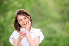 Young smiling woman with mobile phone Royalty Free Stock Photography