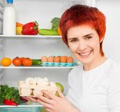 Woman against the refrigerator Royalty Free Stock Photography