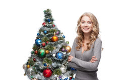 Young smiling woman near christmas tree Stock Photos