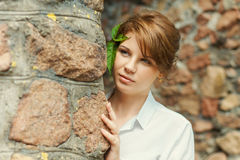 Young smiling woman. Observing behind stone wall Royalty Free Stock Photography