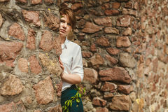 Young smiling woman. Observing behind stone wall Royalty Free Stock Image