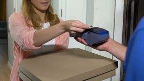 Young smiling woman opening door, taking pizza and paying with credit card stock footage