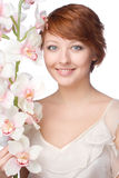 Young smiling woman with orchid Royalty Free Stock Image