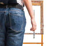 Young smiling woman painter with paintbrush standing at easel Royalty Free Stock Images