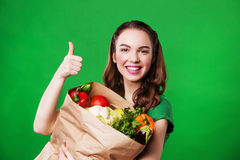 Young smiling woman with a paper bag of vegetables. on green background. Stock Photos