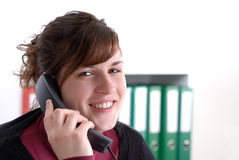 Young smiling woman on the phone in her office Stock Photo