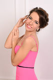 Young smiling woman in pink gown indoors Royalty Free Stock Images