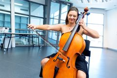 Woman playing cello. Young smiling woman playing cello stock image