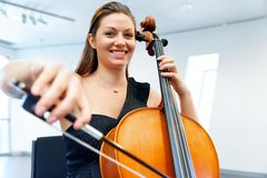 Woman playing cello. Young smiling woman playing cello royalty free stock photo