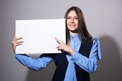 Young smiling woman pointing at a blank white sheet. For advertisement on a gray background Stock Photo