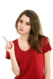 Young smiling woman points a hand with positive facial expressio Royalty Free Stock Images