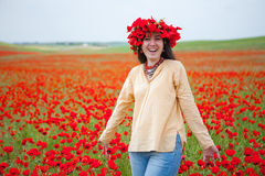 Young smiling woman in poppy field Royalty Free Stock Photos