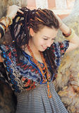 Young smiling woman portrait with dreadlocks dressed in boho style ornamental dress Royalty Free Stock Images