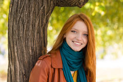 Young smiling woman posing near the tree in park Royalty Free Stock Photo