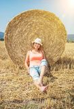 Young smiling woman posing with the stack of straw, sun rays Stock Photo