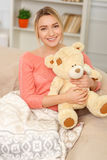 Young smiling woman posing with teddy bear Stock Images