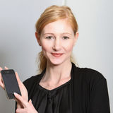 Young, smiling woman presented their smartphone Royalty Free Stock Images