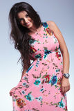 Young smiling woman pulling her pink floral dress. And looking at the camera Stock Image