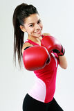 Young smiling woman punching in camera with boxing glove Royalty Free Stock Photos