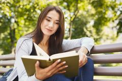 Young woman reading book in park copy space Royalty Free Stock Photos