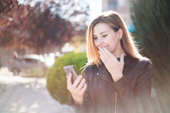 Young smiling woman reading funny message on teletphone. Royalty Free Stock Photography