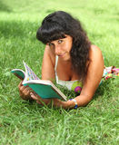 Young smiling woman reading in summer park Royalty Free Stock Photo