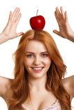 Young smiling woman with red apple on head Royalty Free Stock Images