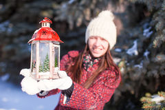 Young smiling woman with red Christmas lantern in winter forest Royalty Free Stock Photography