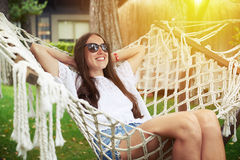 Young smiling woman relaxes in hammock in sunny garden Royalty Free Stock Photo