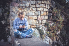 Young smiling woman relaxing outdoors with mobile phone in social media during her travel Stock Photos