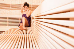Young smiling woman relaxing in a wooden sauna Stock Image