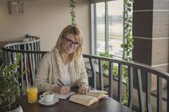Young smiling woman in a restaurant reading a book and taking no stock image