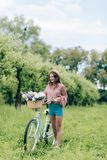 Young smiling woman with retro bicycle with wicker basket full of flowers. In forest royalty free stock photo