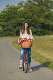 Young smiling woman rides a bicycle Royalty Free Stock Photo
