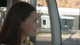 Young smiling woman riding in a tram. Young smiling woman rides the tram and looks out the window stock video