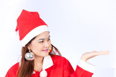 Young smiling woman in santa hat , holds christmas gift Royalty Free Stock Images