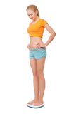 Young smiling woman on scales Royalty Free Stock Photo