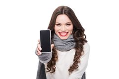 Young smiling woman in scarf and arm warmers showing smartphone screen,. Isolated on white royalty free stock photos