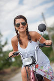 Young smiling woman on scooter with sunglasses and braid hair Royalty Free Stock Photography