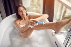 Smiling woman shaving her legs in the bath with foam top view. Young smiling woman shaving her legs in the bath with foam top view royalty free stock photo