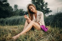 Young smiling woman sits on bevelled meadow. Young smiling woman in shirt and short skirt sits on bevelled meadow stock photography