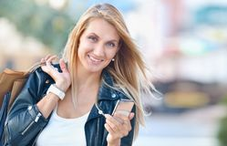 Young smiling woman with shoping bags hold cellular telephone royalty free stock photo