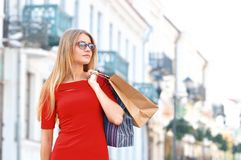Young smiling woman with shoping bags look aside. At old street background. Lifestyle and people concept stock photo