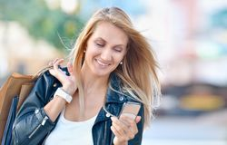 Young smiling woman with shoping bags look at cellular telephone royalty free stock photos