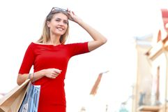 Young smiling woman with shoping bags looking ahead. Young smiling woman with shoping bags on street background. Lifestyle and people concept stock photography