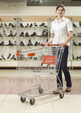 Young smiling woman with shopping cart Royalty Free Stock Photos